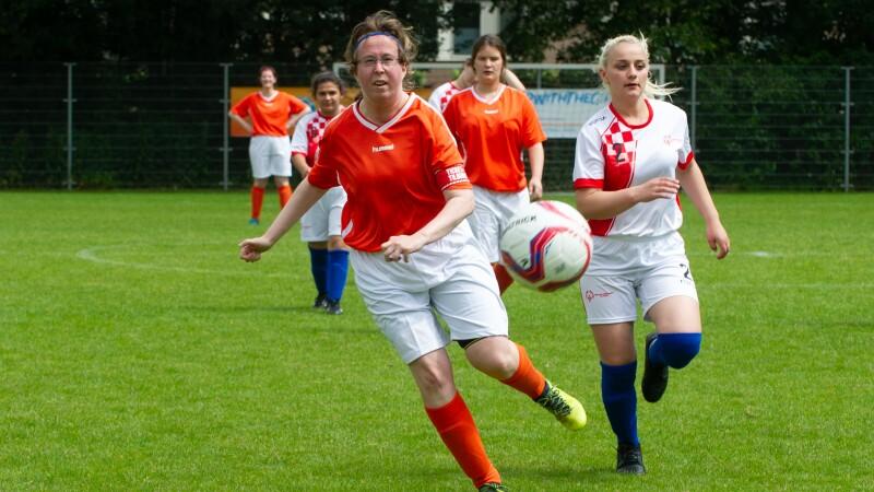 Women in football/soccer jerseys run after a football on a green pitch.