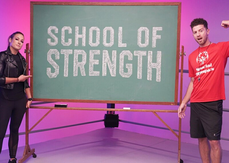 Becky Lynch and Dylan Landon in the ring standing next to a chalk board that reads: School of Strength.