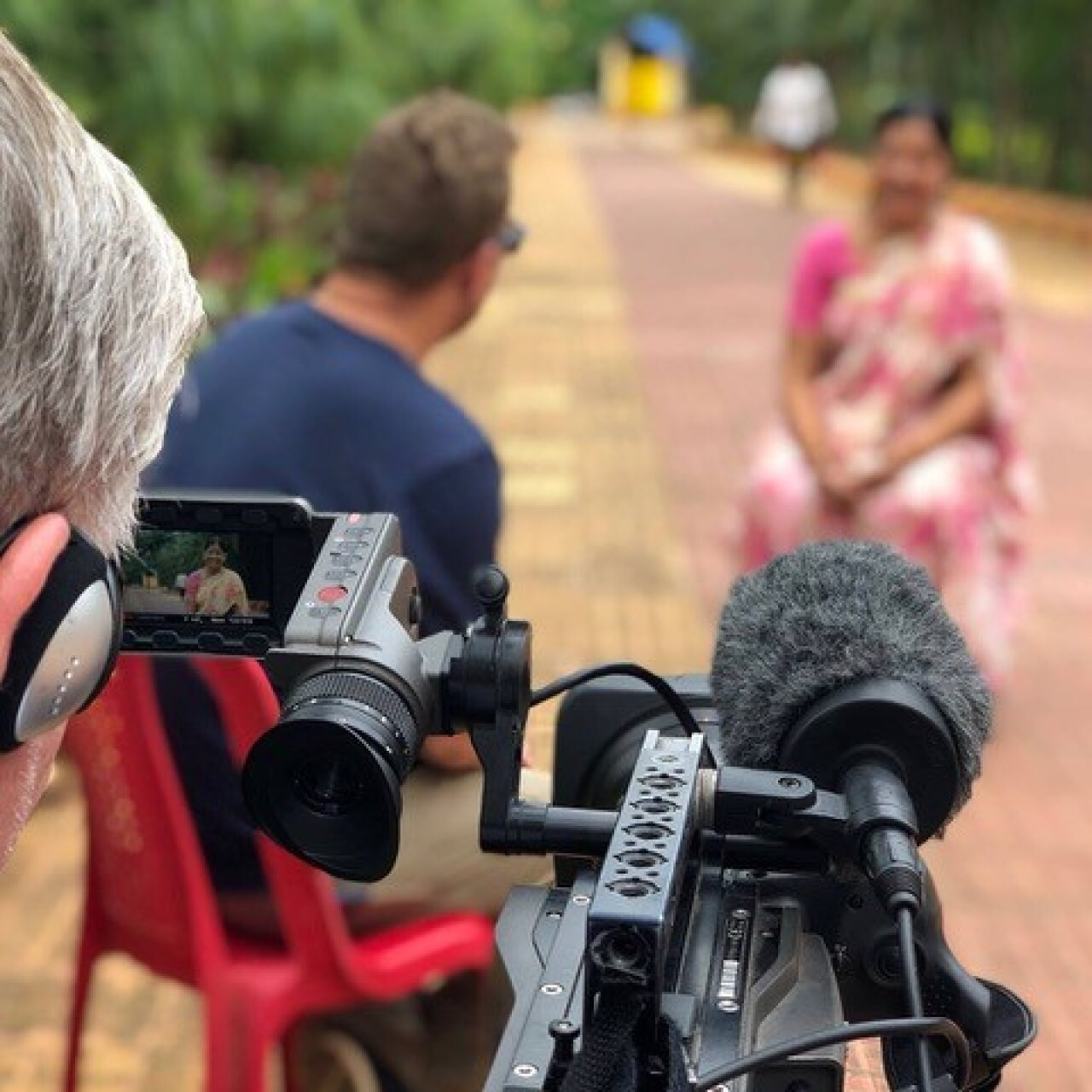 The videographer is focusing his camera on a local woman giving an interview. She is out of focus.