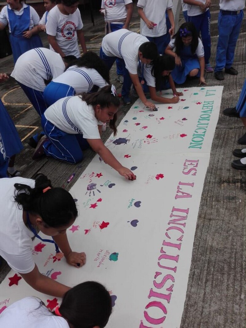 A group of students and athletes sign and decorate an inclusion banner outside.