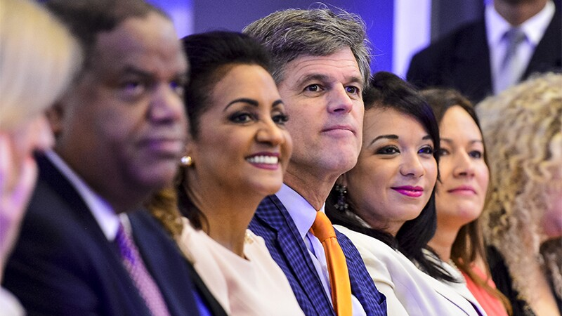 Special Olympics Chairman, Tim Shriver and First Lady of the Dominican Republic, Cándida Montilla de Medina take in the sights from the opening ceremony. They are seated with representatives and leadership on either side of them.