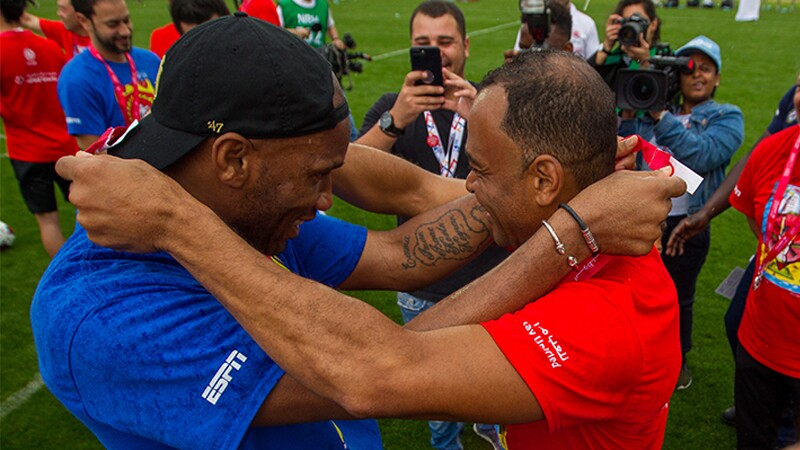 Droba and Cafu on the football field place medals around each others neck at the 2019 world games.