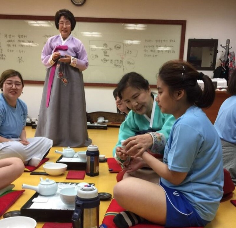 Small group in a room with a white board in the background. Woman standing is wearing kimono, athletes and partners are sitting, speaking, and drinking tea.
