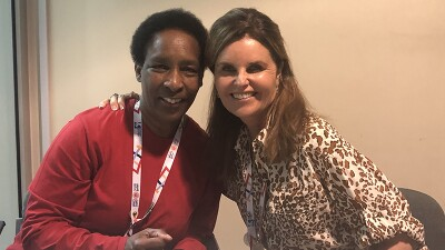 Loretta Claiborne and Maria Shriver sitting down both smiling; Maria has her arm around Loretta's shoulder.