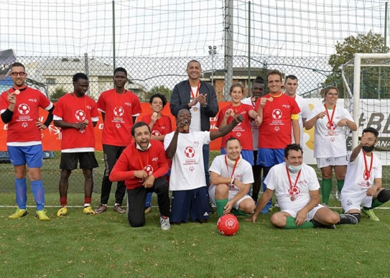 Italian football star David Trezeguet and Unified partner Gerald Mballe celebrating with the other athletes and refugees at the end of the match.
