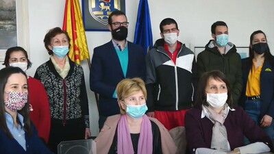 Six people standing behind three women seated, all wearing masks. On the wall in the background, a seal between two flags.