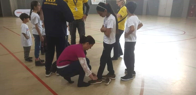 A woman is kneeling down to tie the trainer laces for a young girl who stands beside her. They are surrounded by a small crowd and are on an indoor court.