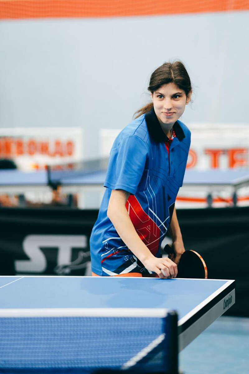 A female athlete standing behind a tennis table, smiling and holding a racket.