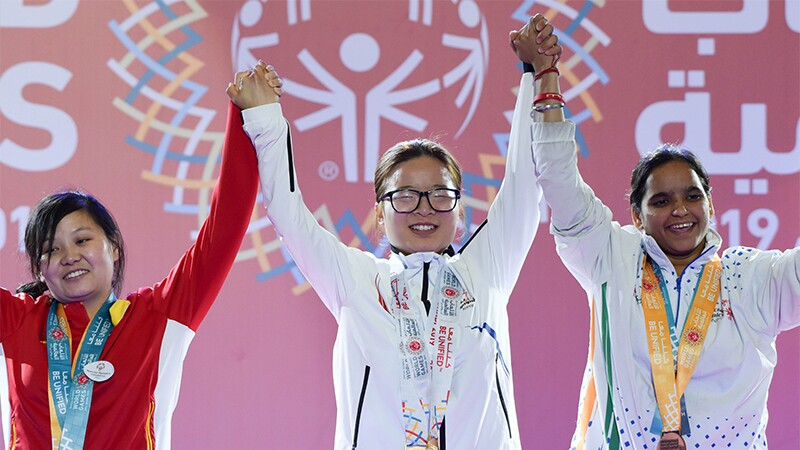 Three athletes at a medaling ceremony holding hands up in the air as a sign of victory.