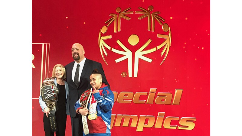 Mary Davis and Special Olympics New York Athlete Angel (power lifter) holding champion ship belts; Big Show standing behind them in front of a Special Olympics sign.