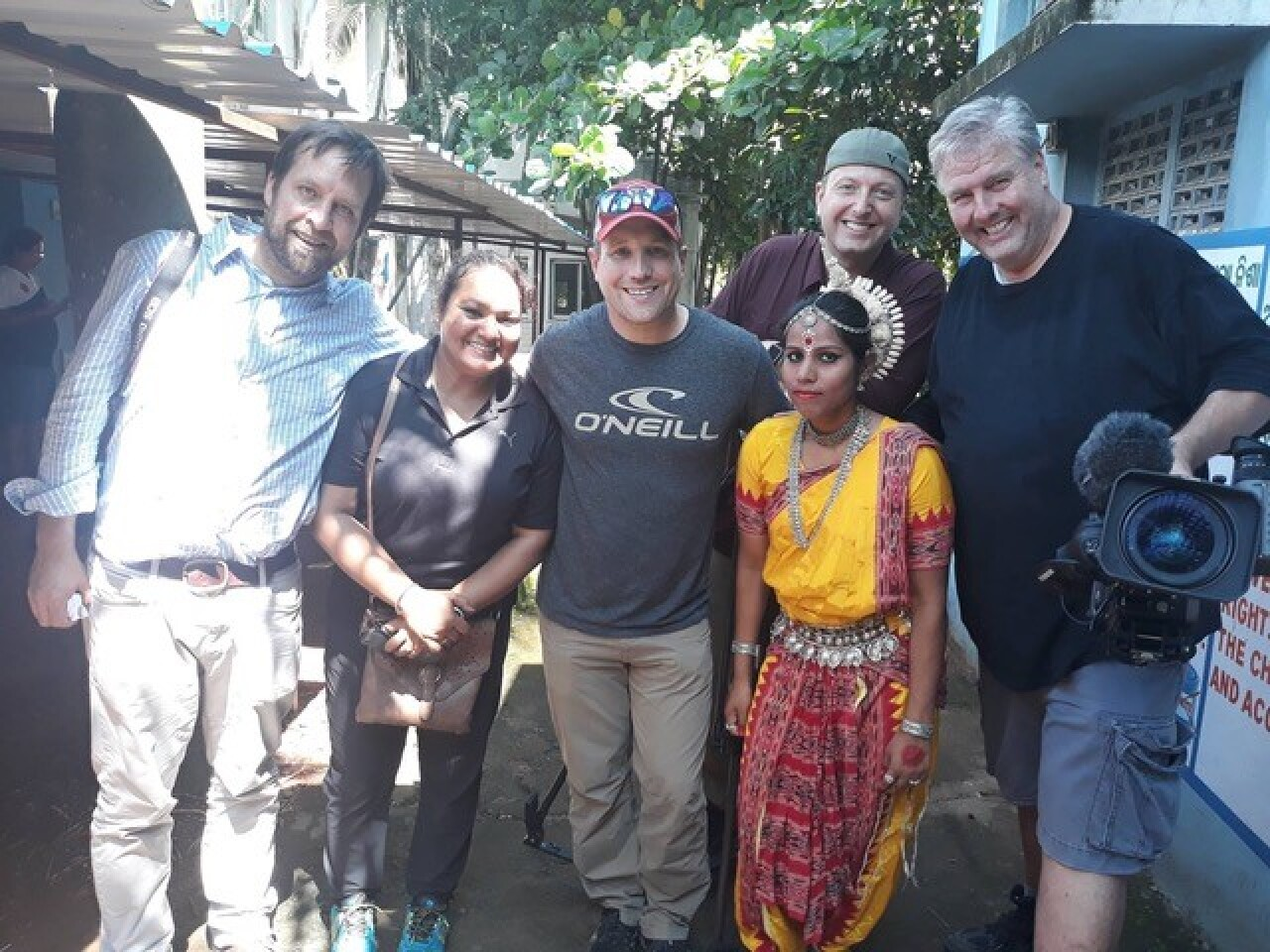 The camera crew consisting of 5 people, 4 male and one female, pose with a local person in a pedestrian area. The local woman is wearing a small decorative head dress, beads, and an ornate and colorful (yellow and red) outfit.