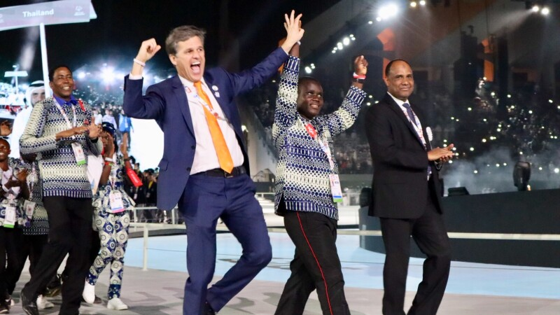 Timothy Shriver with Malachie excited and cheering on the stage at the opening ceremonies. Athletes in the background.