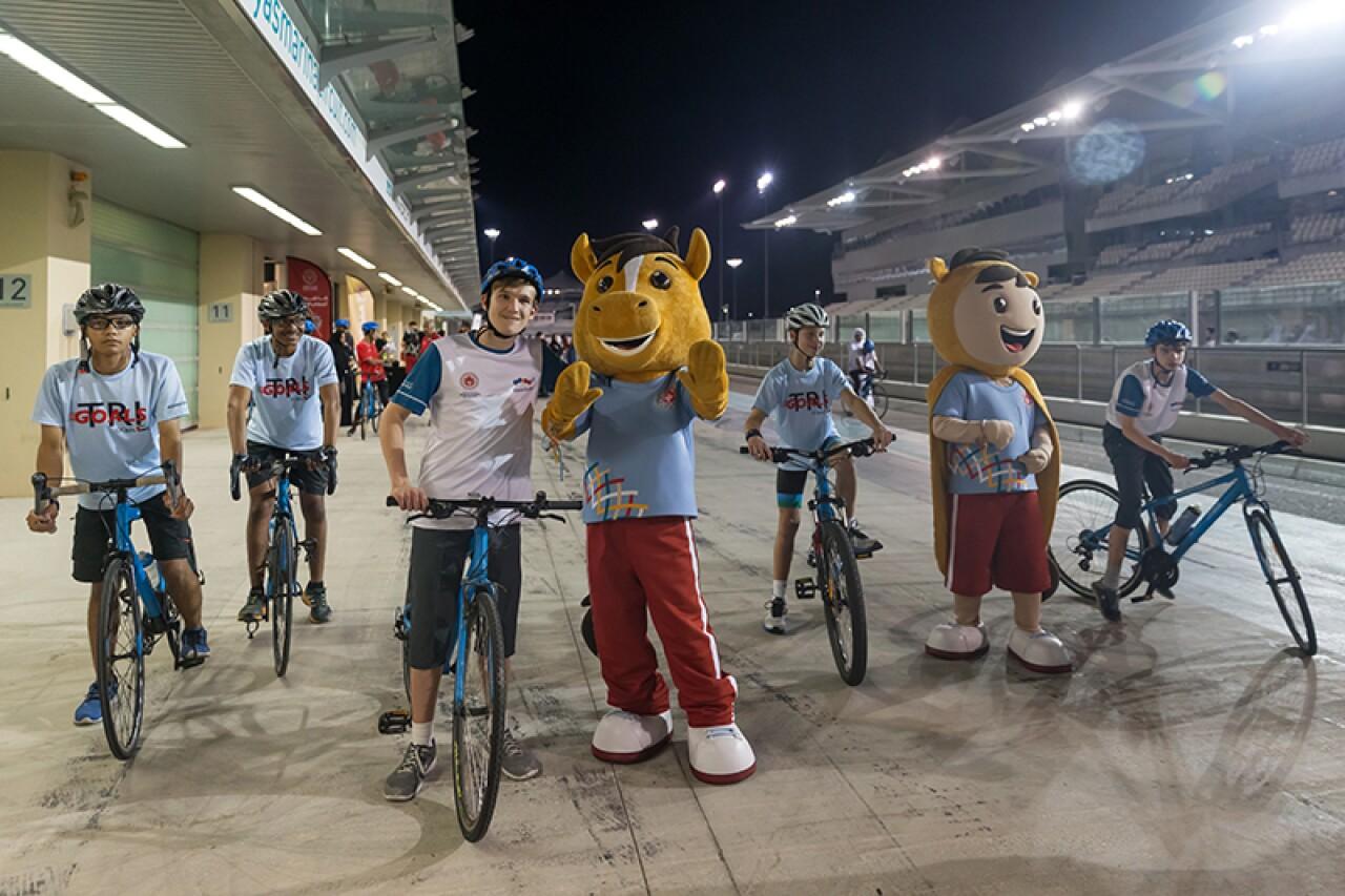 Special Olympics World Games mascots pose with five cyclists.