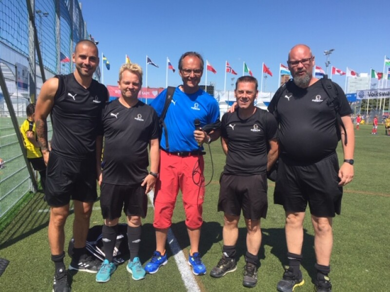 Five men stand in a row smiling and facing the camera on a green pitch with flags in the background. Four of the men are dressed in black t-shirts and shorts with the man in the centre - who is holding a microphone - dressed in red trousers and a blue t-shirt.