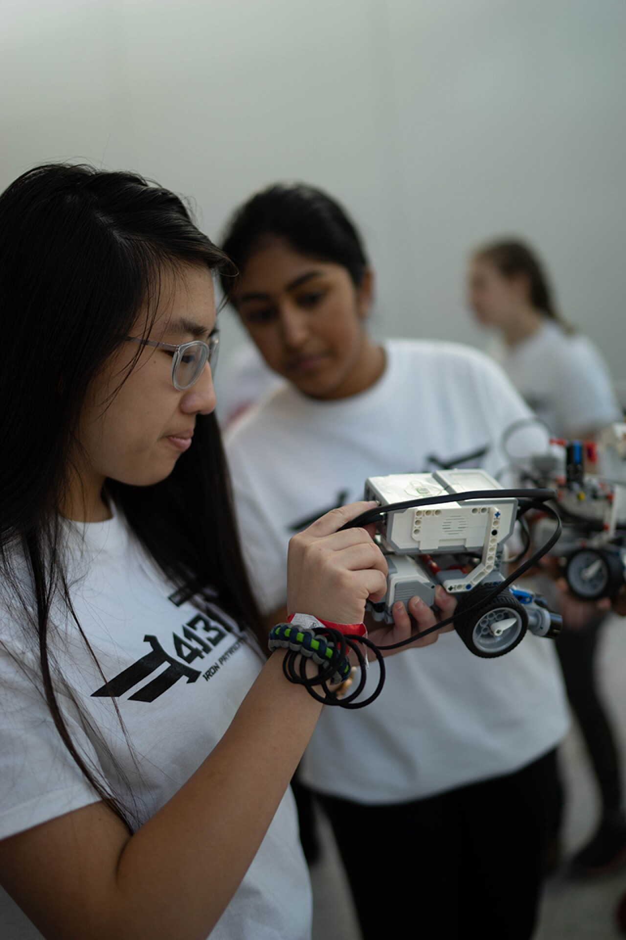 Young lady is tinkering with her robot, an onlooker in the background is watching what she is doing while holding her robot.