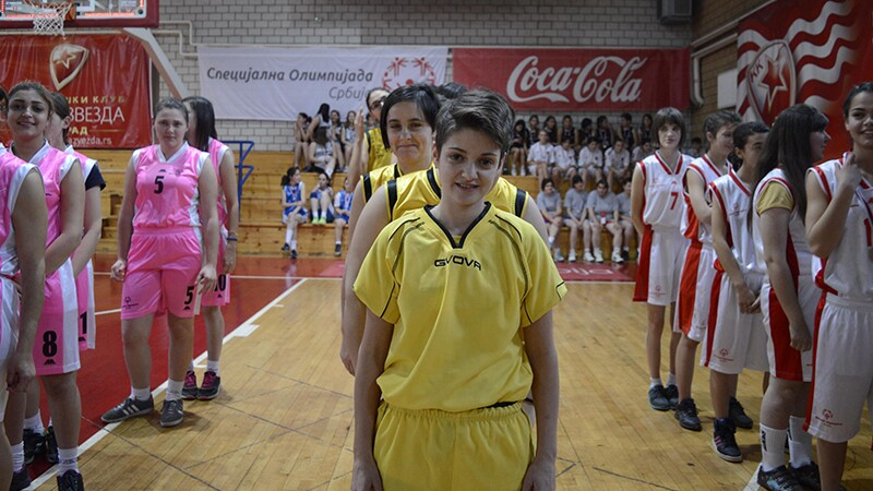 Special Olympics Serbia European Basketball week activities. Three teams of female players are lined up on the court. Far left is wearing pink uniforms, center is wearing yellow uniforms, far right has on white and red uniforms.