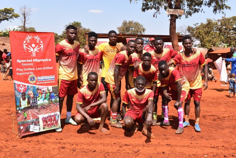 A team of footballers in a yellow and red kit stand together facing the camera alongside a pull-up banner with the Special Olympics Tanzania and Lions Clubs International Foundation logo.