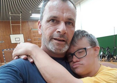 Athlete Kai Bodenstein hugging Coach Rob van Someren Brand in a gymnasium.