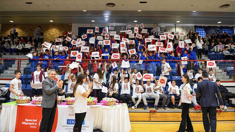 A large crowd of around 50 students sits in stands in an indoor gym, holding up posters for the athletes. They range from elementary to high school-aged. Everyone is smiling and cheering.