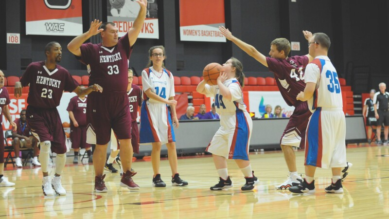 A female player prepares to shoot the ball while males players on the other team attempt to block.