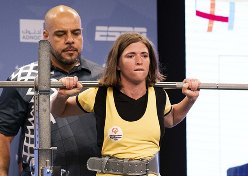 Female power lifter in yellow and black holding a bar on her shoulders, a spotter is behind her.