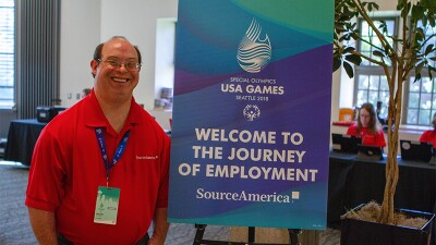 David Egan stands next to a SourceAmerica sign at the 2018 USA Games in Seattle.