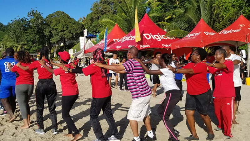 Volunteers and athletes dance together on the sand at the beach at the 2018 Beach Games in Trinidad.