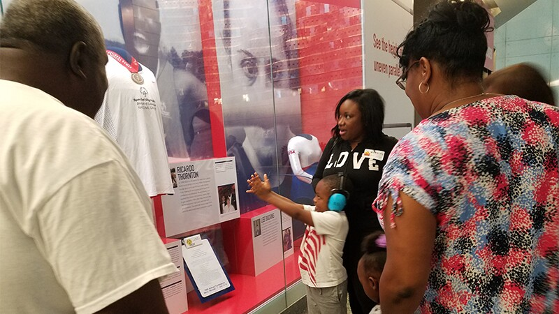 """Ricardo Thornton with Seth Rogers at the National Museum of American History's """"Morning at the Museum"""" program. A young child is looking at Ricardo's display with people in the background."""