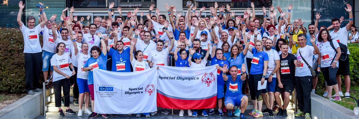 Large group of people standing outside for a group photo holding a Stavros Narchos Foundation and Special Olympics Banner.