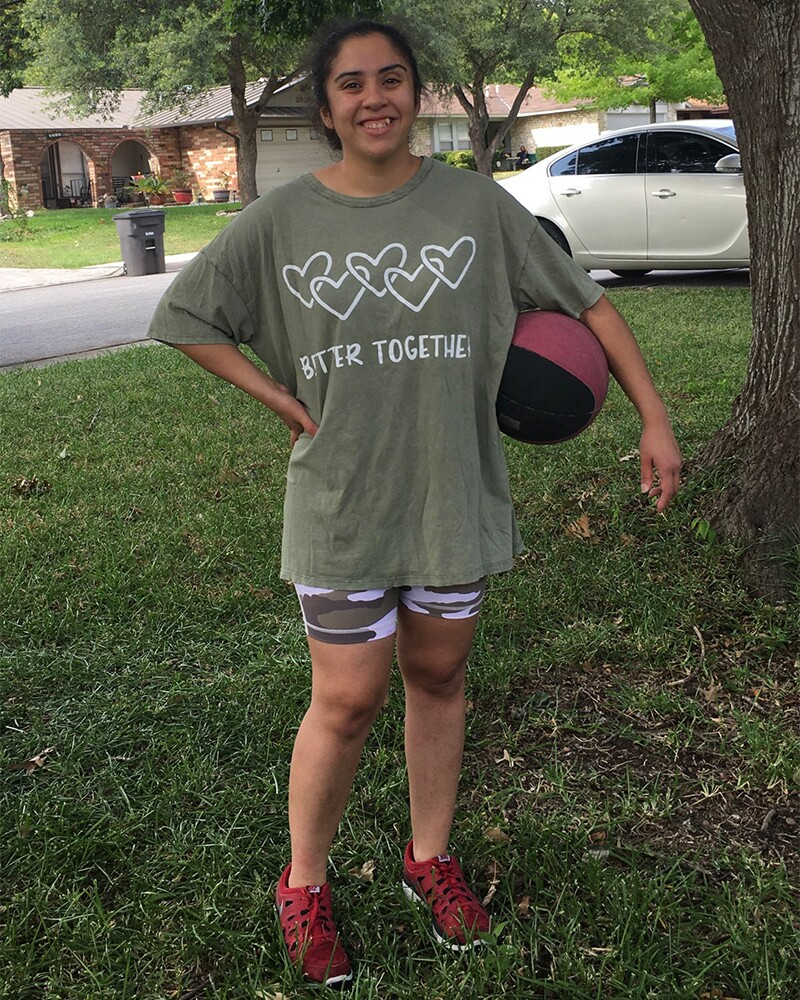 Magdalena Robles outside with a ball under her left arm in a green Better Together t-shirt.