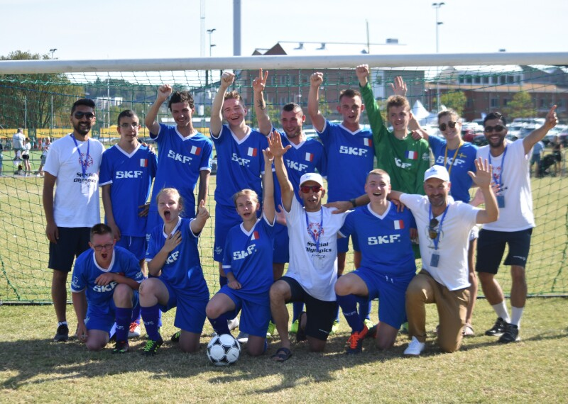 A team in blue football kits gather together in front of the goals on a pitch with their hands in the air.