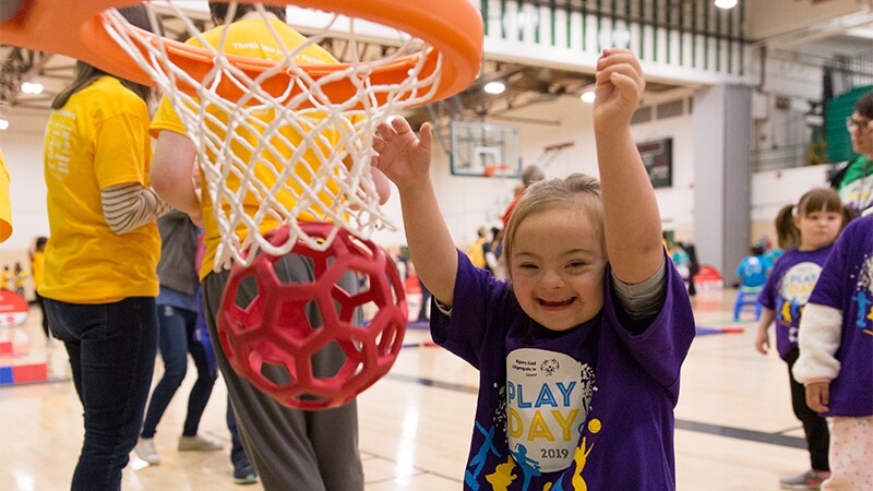 Young athlete with Down syndrome playing basketball.