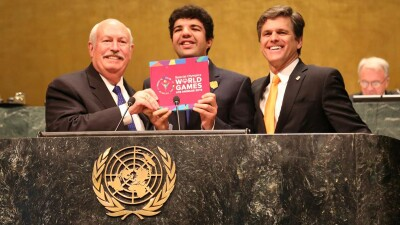 Bob Corlew, Dr. Timothy Shriver, and Special Olympics athlete Mina Baghat standing at a podium at the United Nations.