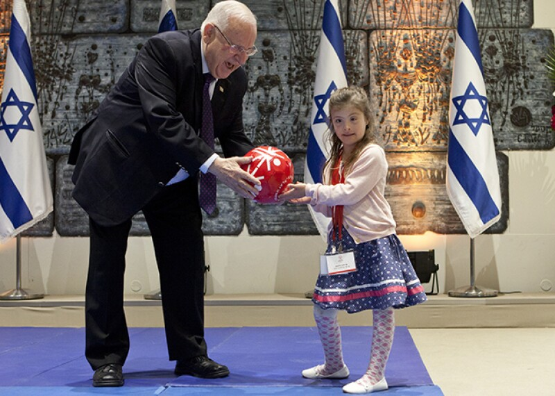 Shay Dagan Plessman presenting Israeli President Reuven Rivlin with a Special Olympics football.