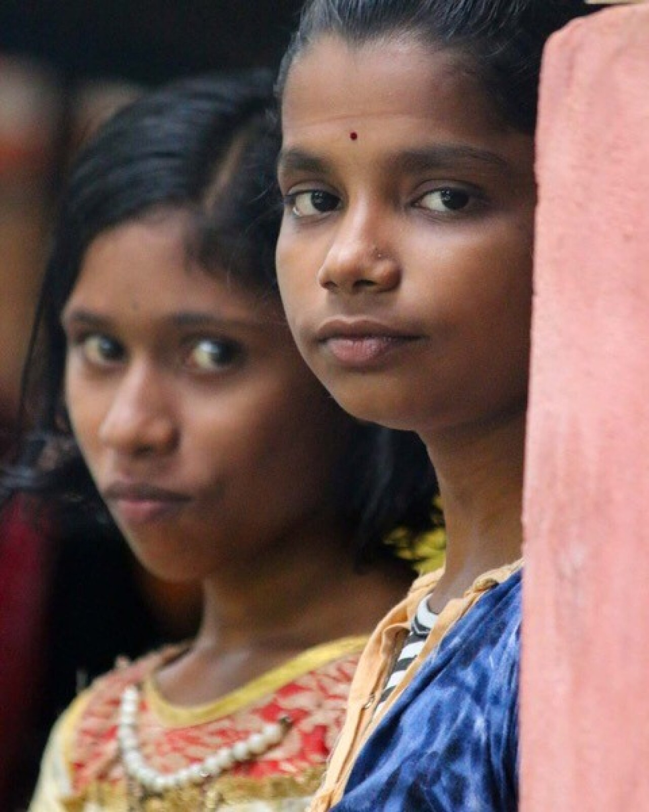 Two young girls are looking at at the photographer. The young girl in the background is wearing a colorful yellow, red, white, and gold top and the young girl in the foreground is wearing a colorful blue top.