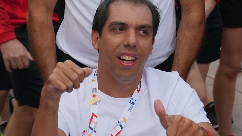 Special Olympics swimmer, Aquiles Heredia enters the Global Village with the Venezuelan delegation