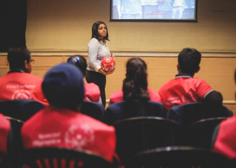 Woman standing in from of a group of people giving a presentation and holding a Special Olympics football.