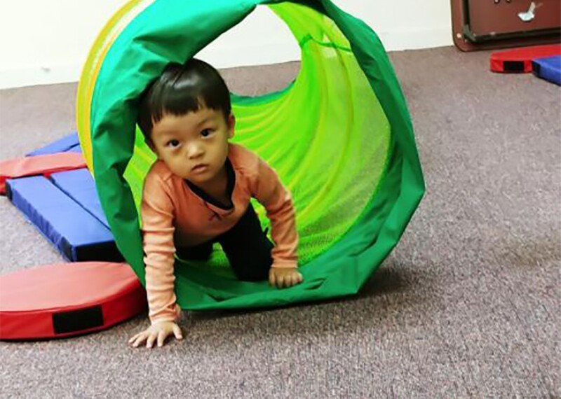 Young boy crawling through a fabric collapsible tube.