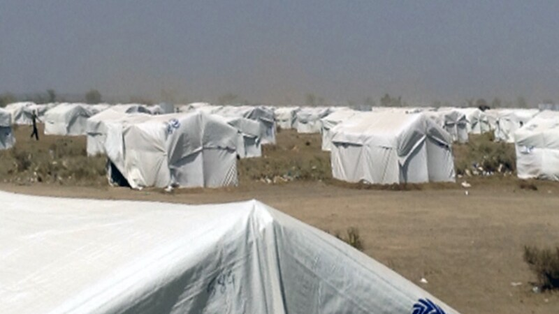 10s of white tents with the UN High Commissioner for Refugees logo on them lay in an expansive field.