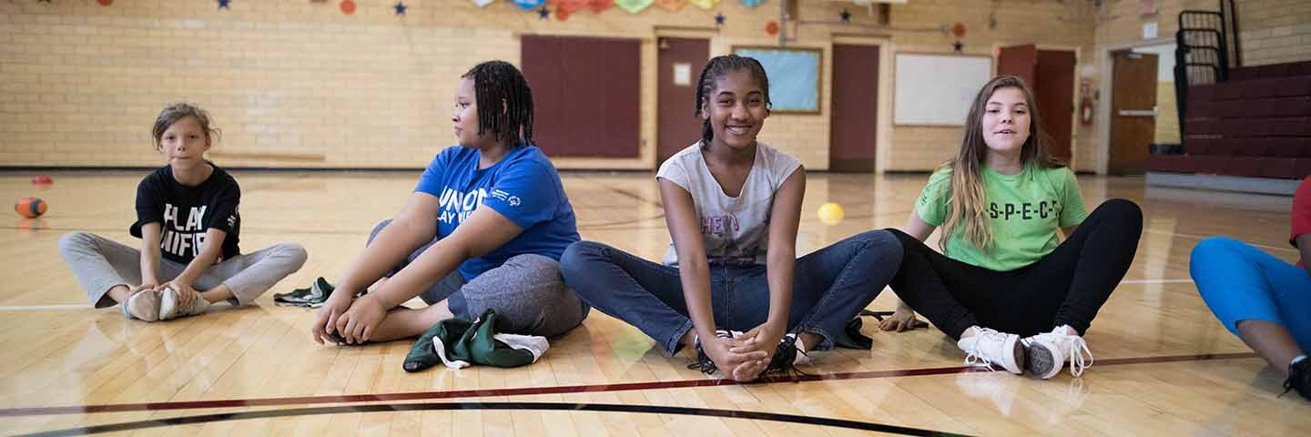 Four young girls in the gymnasium sitting on the floor stretching out.