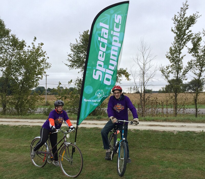 Daniel Smrokowski with friend Georgis in helmets and purple event shirts sitting on bicycles in front of a Special Olympics Illinois marker flag.