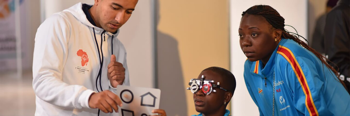 Athlete being given an eye exam by a volunteer and an observer watching.
