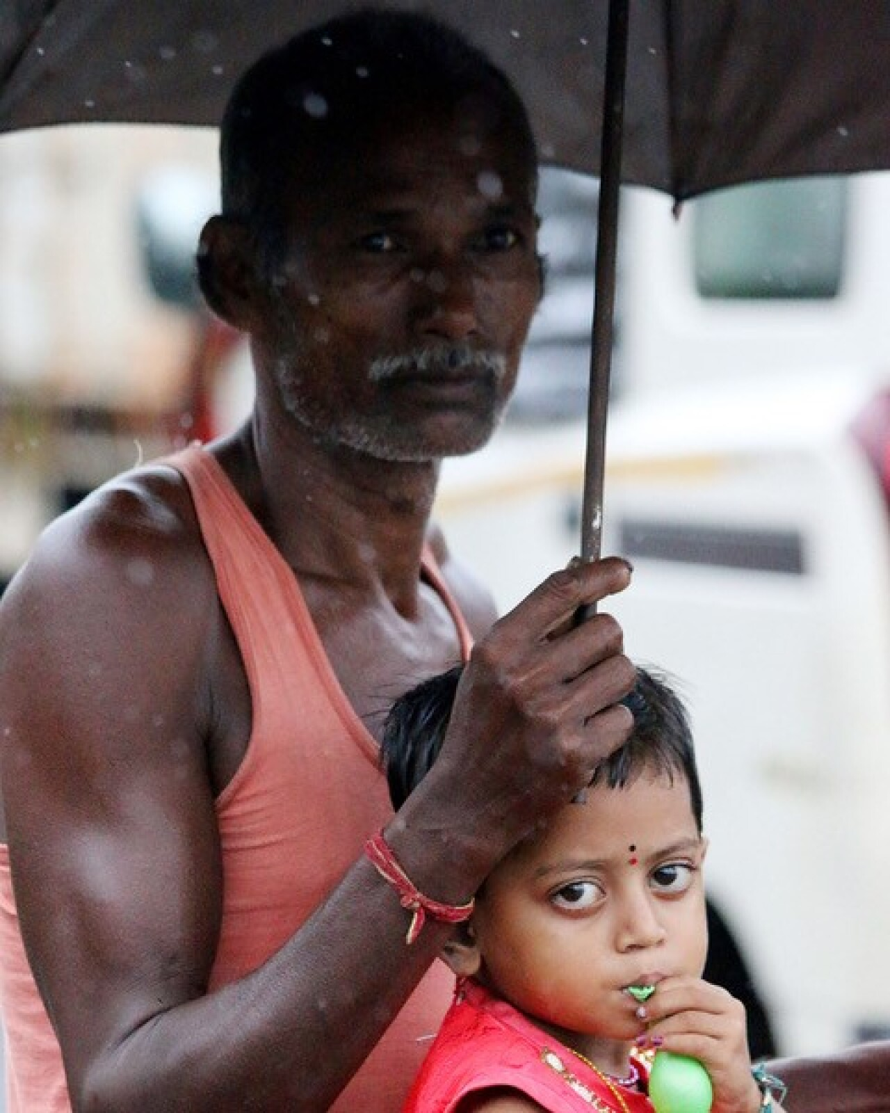 and older man is holding an umbrella to cover himself and a young boy from the rain.