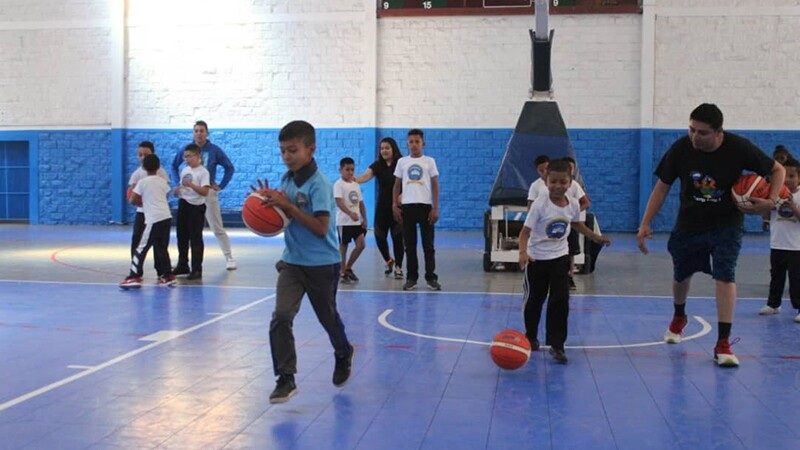 Young athletes practicing basketball on the court.
