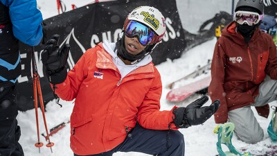 Latrice in and orange ski jacket on one kneed posing for the camera on the slopes.