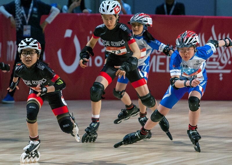 Four rollerbladers racing on a track.