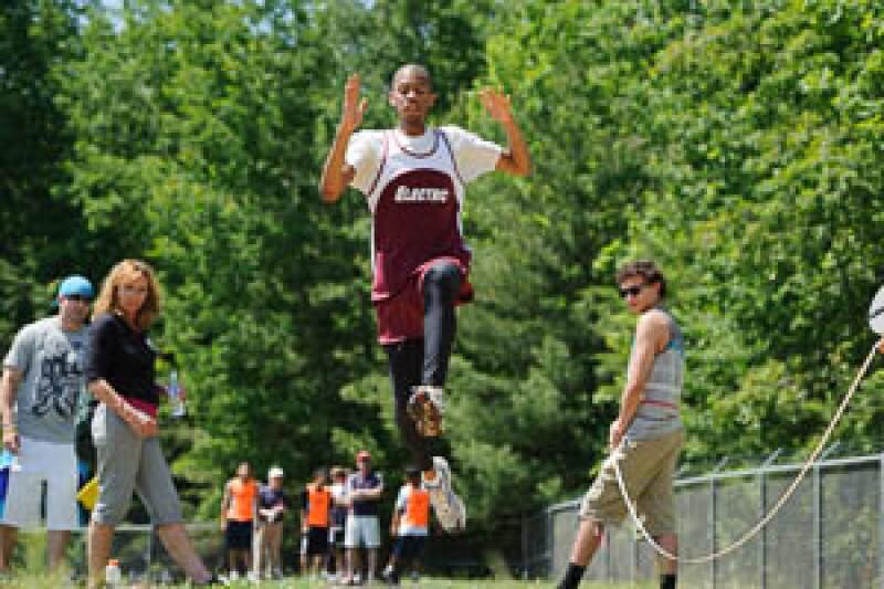 Volunteers watch and measure long jump distances.