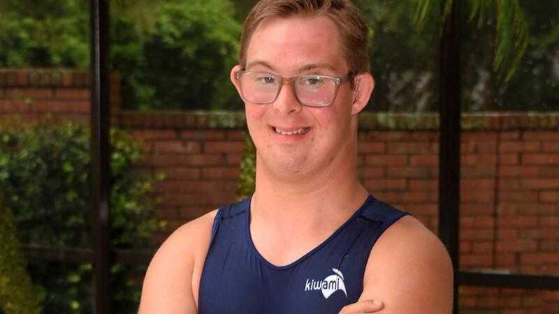 Chris Nikic smiling with his arms crossed and in his Special Olympics Florida tank-top.