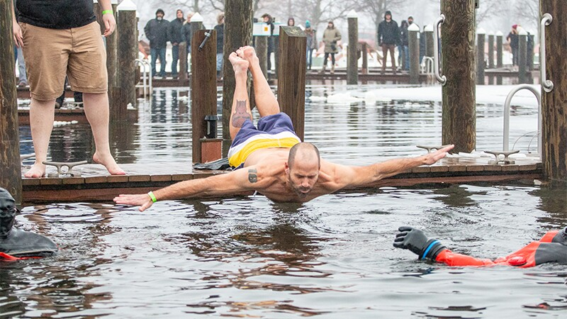 Man jumping off a dock and doing a belly flop as onlookers watch.