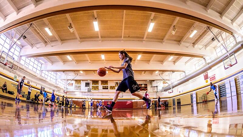 Ashely Aldrich running across the basketball court dribbling the ball.